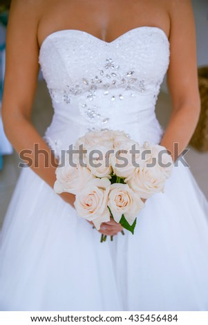 Beautiful, sophisticated bride with pink roses bouquet