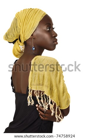beautiful South African young woman with head wrapped in traditional style yellow scarf looking seriously in profile. - stock photo