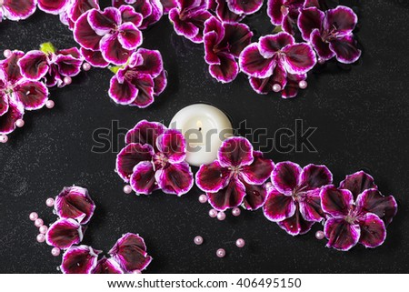 beautiful spa background of geranium flower, beads and candle in reflection water - stock photo