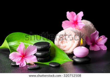 beautiful spa background of pink hibiscus flowers, green leaf, candle, towel and stones pyramid with drops, closeup - stock photo