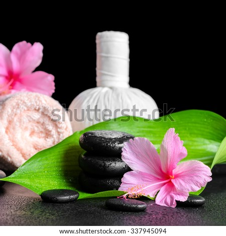 beautiful spa background of pink hibiscus flowers, leaf, towel, thai herbal compress ball  and stones with drops, closeup - stock photo