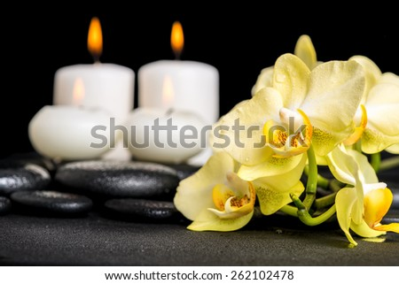 beautiful spa background of yellow orchid phalaenopsis and candles on black zen stones with drops - stock photo