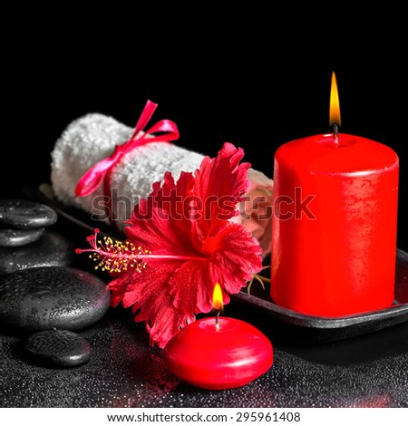beautiful spa composition  of hibiscus flower with dew, red candles and white rolled towel tied with ribbon on zen stones, closeup - stock photo