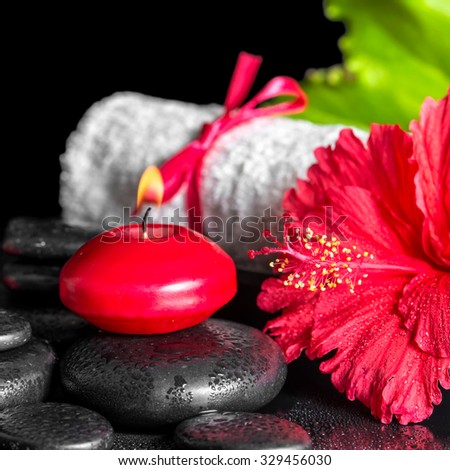 beautiful spa composition of red hibiscus flower with dew, candles, green leaf and rolled towel tied with ribbon on zen stones - stock photo