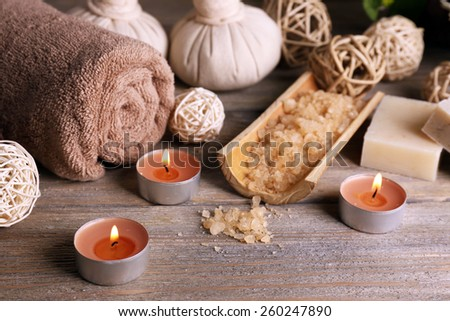 Beautiful spa composition with sea salt and candles on wooden background