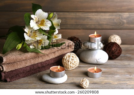 Beautiful spa composition with stones and flowers on wooden background