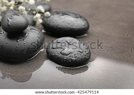 Beautiful spa composition with wet stones and flowers on grey background - stock photo