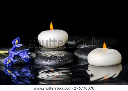 beautiful spa concept of blooming iris flower, candles and black zen stones on ripple reflection water, closeup  - stock photo
