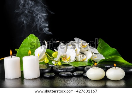 beautiful spa concept of blooming white orchid flower, phalaenopsis, green leaf with dew, smoke stick and candles on black zen stones, close up