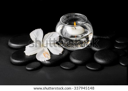 beautiful spa concept of dew white hibiscus flower and candles in vase with water on zen stones, closeup - stock photo