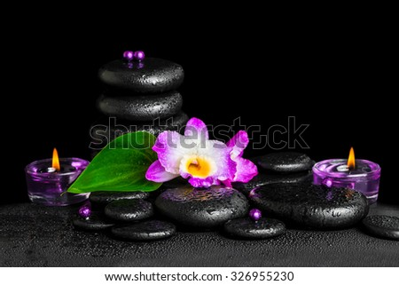 beautiful spa concept of purple orchid dendrobium with dew, pyramid black zen stone, green leaf, beads and lilac candles, closeup  - stock photo