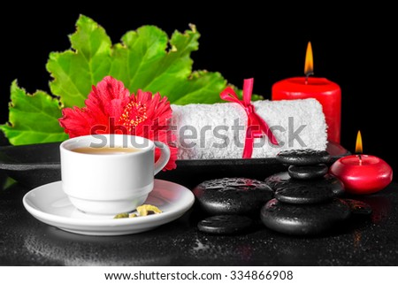 beautiful spa concept of red hibiscus flower with dew, candles, green leaf, cup of tea and rolled towel on zen stones - stock photo