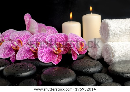 Beautiful spa concept of zen stones with drops, blooming twig of stripped violet orchid (phalaenopsis ), candles and stacked of towels - stock photo