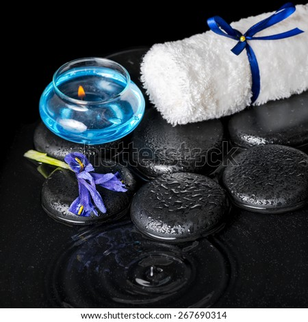 beautiful spa concept top down of iris flower, blue candle, white towel and black zen stones on ripple reflection water, closeup - stock photo