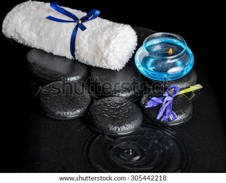 beautiful spa concept top down of iris flower, blue candle, white towel and black zen stones on ripple reflection water - stock photo