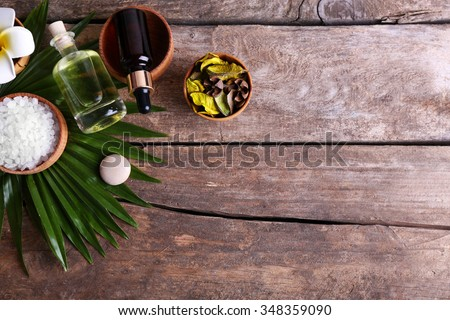 Beautiful spa setting on palm leaf on wooden table - stock photo