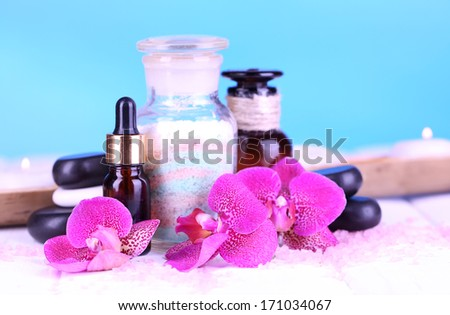 Beautiful spa setting with orchid on white wooden table on blue background