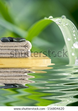 Beautiful spa setting with towel and massage rocks on tranquill nature scene. - stock photo