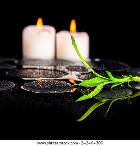 beautiful spa still life of green twig bamboo and candles on zen basalt stones with dew in reflection water, closeup - stock photo