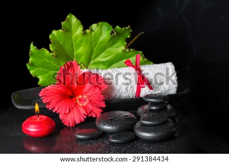 beautiful spa still life of red hibiscus flower with dew, candles, green leaf, scent stick and rolled towel on zen stones - stock photo