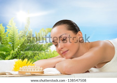 beautiful spa woman lying on the couch, in front of her flower and rolled towel - stock photo