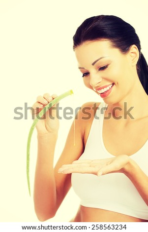 Beautiful spa woman squeezing juice from aloe vera. - stock photo