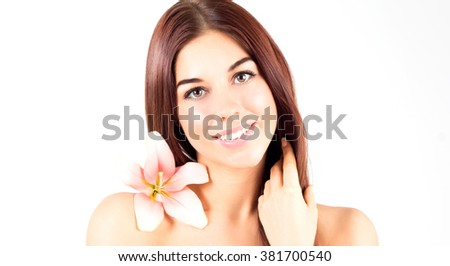Beautiful spa woman touching her hair. Woman with pink flower smiling with white teeth. Woman with fresh and clear skin.