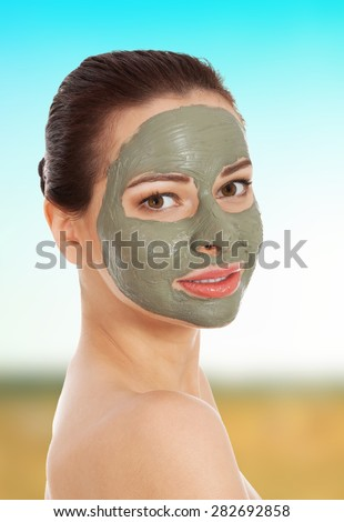 Beautiful spa woman with clay facial mask. - stock photo