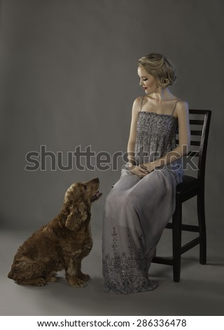 Beautiful Spaniel dog sitting at the feet of a lovely blonde woman wearing a gray dress - stock photo
