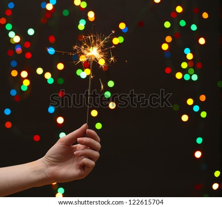 beautiful sparkler in woman hand on garland background - stock photo