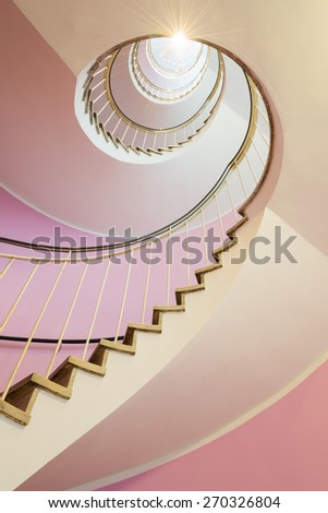 Beautiful spiral staircase with pink walls - stock photo
