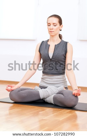 Beautiful sport woman doing stretching fitness exercise at sport gym. Yoga lotus pose