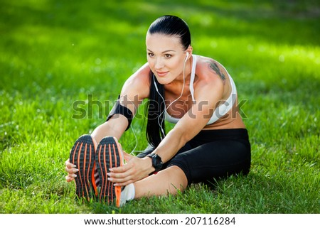 Beautiful sport woman doing stretching fitness exercise in city park at green grass. Yoga postures - stock photo