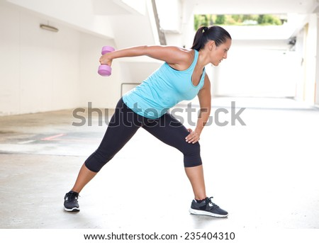 Beautiful sport woman in blue with dumbbell doing tricep back extension exercise - stock photo