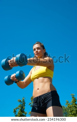 Beautiful sport woman with dumbbells on playground, background of green trees in park and blue sky