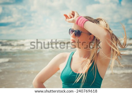 Beautiful sportive girl with long blond ponytail and white skin at the beach. Selective focus.