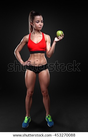 Beautiful sportly fitness girl holding an apple - stock photo