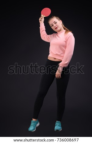 Beautiful sports lady dressed in a black leggings and pink sweater