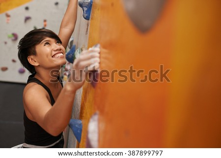 Beautiful sportswoman enjoying every step up the climbing wall