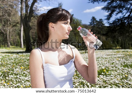 beautiful sporty caucasian girl holding bottle of water after exercise