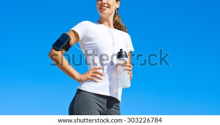 beautiful sporty caucasian woman hold bottle outdoor - stock photo