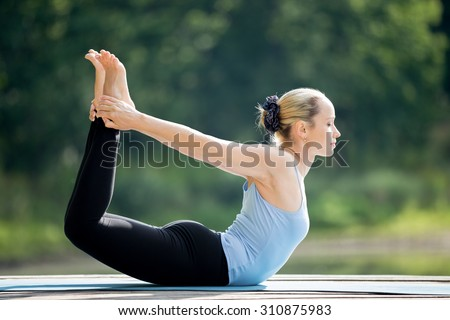 Beautiful sporty fit blond young woman wearing blue tank top sportswear working out outdoors on summer day, doing basic posture Dhanurasana, Bow Pose, full length