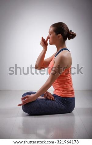 Beautiful sporty fit yogini woman practices pranayama breath control exercise in yoga asana Padmasana - lotus pose with Vishnu mudra in studio - stock photo