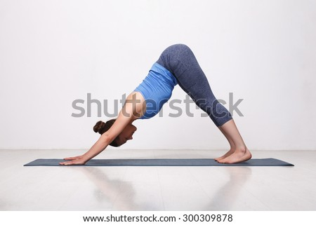 Beautiful sporty fit yogini woman practices yoga asana adhomukha svanasana - downward facing dog pose in studio - stock photo