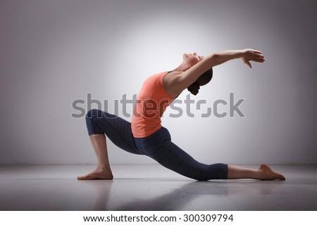 Beautiful sporty fit yogini woman practices yoga asana  Anjaneyasana - low crescent lunge pose in surya namaskar in studio - stock photo