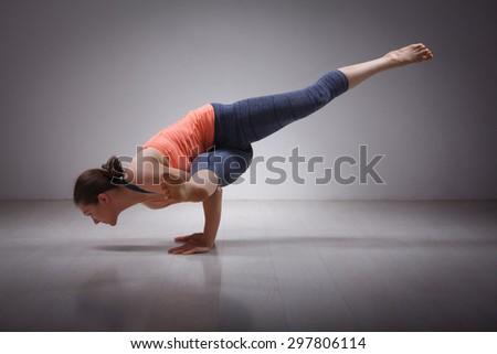 Beautiful sporty fit yogini woman practices yoga asana eka pada koundinyasana 1 - pose 1 dedicated to sage Koundinya pose in studio - stock photo