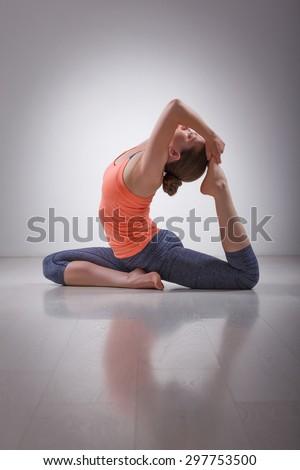 Beautiful sporty fit yogini woman practices yoga asana Eka pada rajakapotasana - one-legged king pigeon pose in studio - stock photo