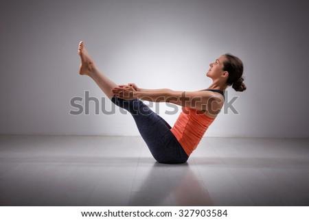 Beautiful sporty fit yogini woman practices yoga asana Paripurna navasana - boat pose - stock photo