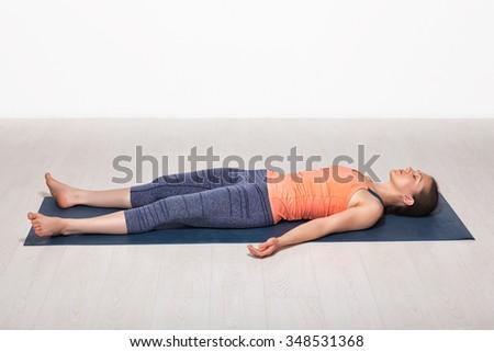 Beautiful sporty fit yogini woman relaxes in yoga asana Savasana - corpse pose in studio - stock photo