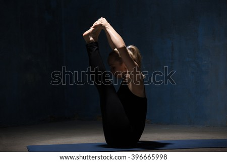 Beautiful sporty fit young woman in black sportswear working out indoors against grunge dark blue wall. Model sitting in Ubhaya Padangusthasana, Both Big Toe posture. Full length